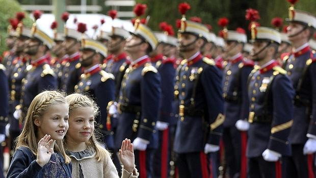 La Princesa de Asturias saluda, junto a su hermana Sofía en el desfile de la Fiesta Nacional,
